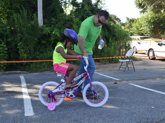 """FILE -- David Laborde (right) of the Laborde Earles Law Firm helps Marlexia Sanders navigate the course on her new bike during the """"Bike It Forward"""" event in 2015."""