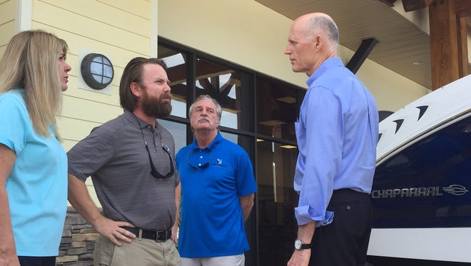 Gov. Rick Scott, right, meets with Diane Fricke, left, the owner of Fish Tale Boats in Lee County, and her son Travis Fricke, center, the company's vice president of operations on Tuesday, May 30, 2017.