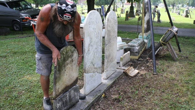 """John """"Walt"""" Walters and his crew of graveyard groomers work on stones dating back to the mid-1800s during restoration work at New Albany's 150-year-old Fairview Cemetery on Wednesday."""