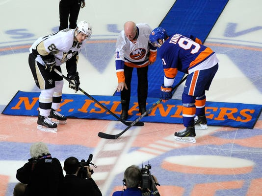 New York Islanders former goalie Billy Smith drops a ceremonial puck between Pittsburgh Penguins center Sidney Crosby (87) and New York Islanders center John Tavares (91) in the first period of an NHL hockey game at Nassau Coliseum on Saturday, Nov. 22, 2014, in Uniondale, N.Y. (AP Photo/Kathy Kmonicek)