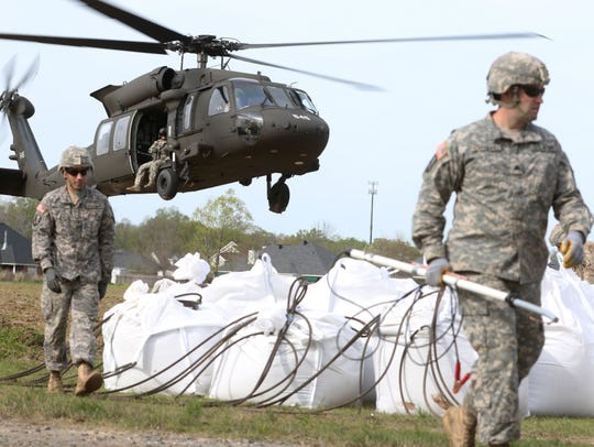 The Louisiana National Guard conducts a sling-load operation to drop bags of sand called super sacks into the flood control structure behind Town and Country subdivision in Monroe on March 15, 2016.