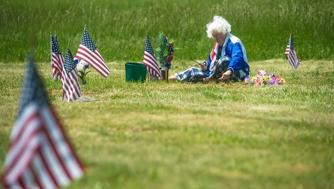 Marian Berry of Carlisle uses a garden trowel to straighten the area around her husband's grave at Oak Lawn Memorial Gardens. Her husband, John H. Berry, was a Vietnam veteran who died in 2009. Berry is angry about the state of the cemetery and plans to move his remains in the near future. 'He's going as soon as I can get him out of here.'