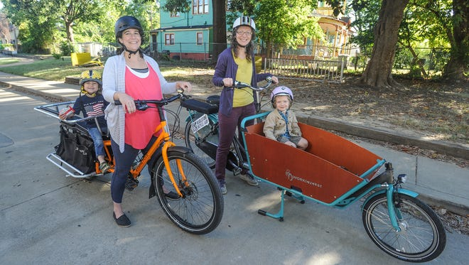 Ellen Cumba (left) and her son, Alijah, ride to Peabody Elementary School with founder of Revolutions Bicycle Cooperative, Sylvia Crum and her son, Charlie, several days per week.