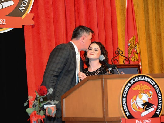 "Staff Sergeant John Jones kisses his daughter, Jade Jones, after giving an emotional speech about her for the Marine Corps Scholarship Foundation. ""My love for him grows more and more every day and I'm just very grateful for him as a father and as a role model,"" Jade Jones said."