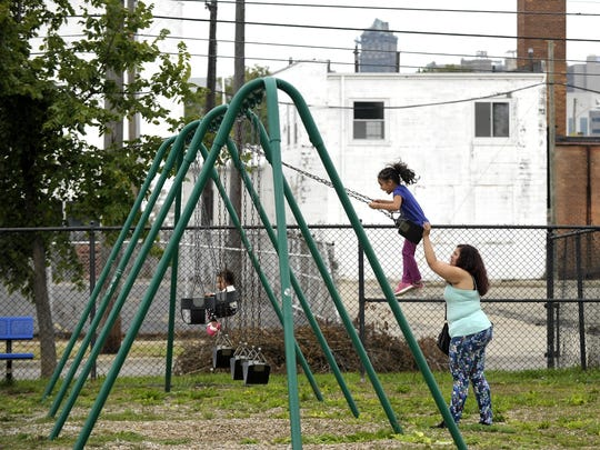 Gloria Galvan pushes daughter Gloria Rocha-Galvan as niece Idiana Delgado waits in September near the former Lincoln Brass Works factory in Corktown. Potentially cancerous fumes wafting from that site a year earlier prompted the evacuation of 80 kids and 144 adults from a pre-school.