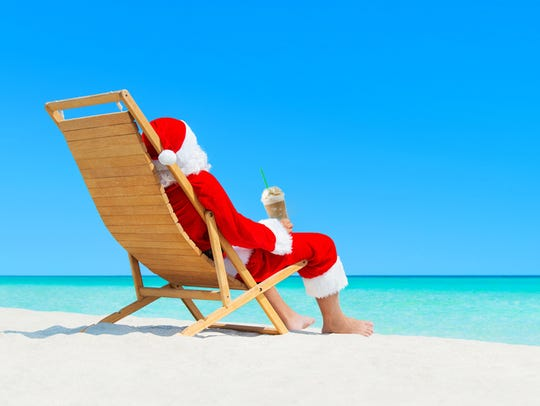 Christmas Santa Claus resting on wooden deckchair with