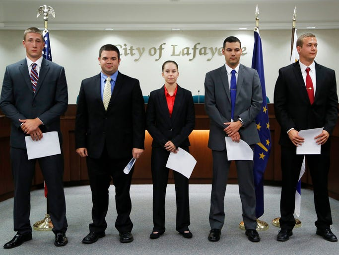 Dustin Rusk, from left, Evan McCain, Cassandra Leuck, Joe Dorrell and Neil Chidalek are applauded by a standing room only crown after being sworn in as officer with Lafayette Police Department Friday, August 8, 2014, in the Lafayette City Council Chambers.