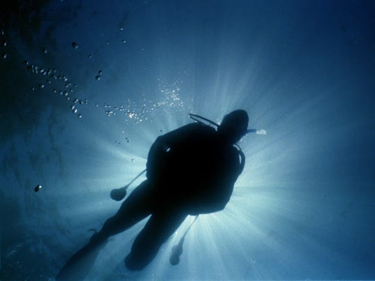 A diver is silhouetted as he swims over the wreck of a barge in Emerald Bay, Lake Tahoe.