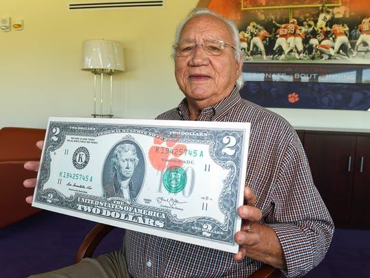 George Bennett holds a large copy of a two dollar bill with a Clemson Paw at Clemson on Tuesday, September 26, 2017. Bennett started the tradition of Clemson fans spending two dollar bills on road games.