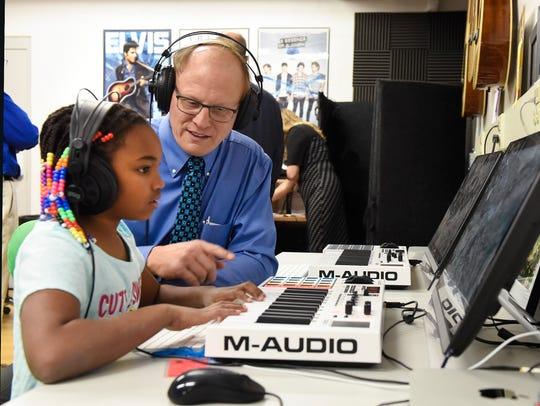 Precious Robinson, 8, shows Tom Wicks, director of