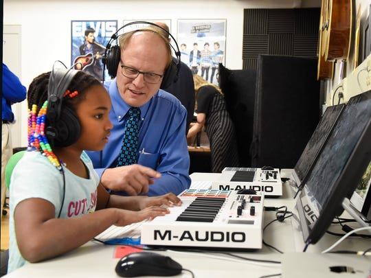 Precious Robinson, 8, shows Tom Wicks, director of programing for the Boys & Girls Clubs of Central Minnesota, how to create music on the computer Wednesday, Nov. 1, at the Southside location.
