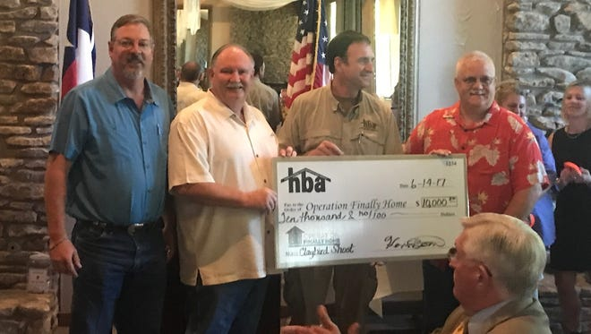 From left: Brian Underwood, Michael Biggerstaff and Kevin Bond, of the Home Builders Association of San Angelo, present a check for $10,00 to Ronnie Lyles, project manager for Operation Finally Home, at the group's June luncheon.