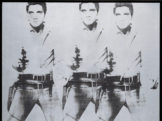 """This undated photo provided by Christie's shows Andy Warhol's """"Triple Elvis (Ferus Type),"""" which is going on the auction block at Christie's in New York this November. The Elvis, executed in ink and silver paint in 1963, depicts the rock 'n' roll heartthrob as a cowboy, armed and shooting from the hip."""