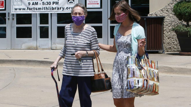 Betty Graves, left, gets help carrying her books to the car at the Fort Smith Main Library by Miller Branch Manager Tiffany Devries. The Main Library is the only operating library in Fort Smith due to COVID-19 and only accepts a number of patrons per hour through appointments. The library is open 9 a.m. to 5 p.m. Monday through Friday. More information is available at www.fortsmithlibrary.org.