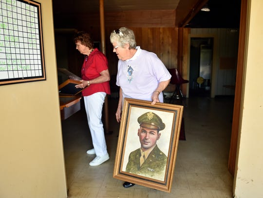 Becky Hively, center, carries a portrait of her cousin