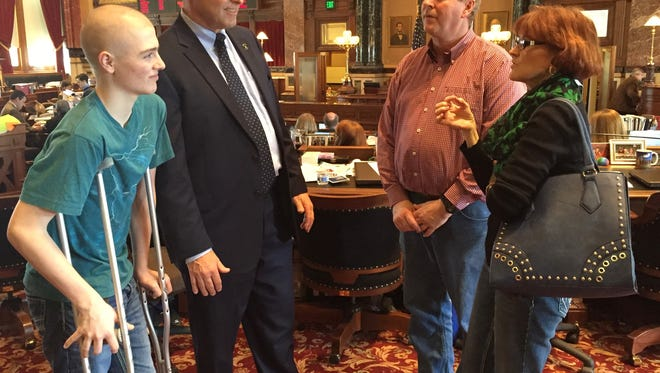 Jacy McAlexander, 15, at left, visits the Iowa Senate chamber Wednesday with his mother, Kerri, and father, Earl. They talked with state Sen. Tim Kraayenbrink, R-Fort Dodge, who was standing next to Jacy. The cancer stricken youth, who also has a broken leg, climbed to the top of the Capitol dome on Wednesday.