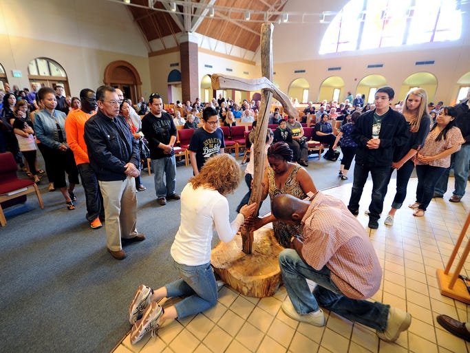 People gather to venerate the cross during the Good Friday liturgy at St. Monica Catholic Church, Friday, April 18, 2014, in Indianapolis. The church conducted the liturgy in English and Spanish for the families that belong to the church.