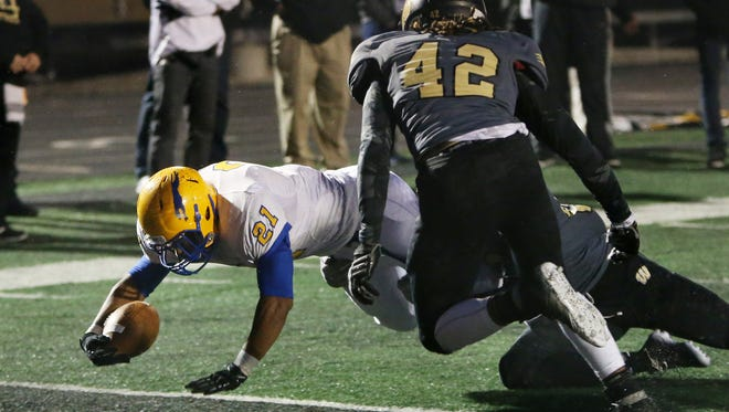 Carmel's Chris Perkins scores the Greyhounds' second unanswered touchdown in the first quarter past Warren Central's Tyan Young as the numbers 1 and 2 Class 6A teams, respectively, play on Friday, October 10, 2014. Carmel took a 14-10 lead into halftime at Warren Central.