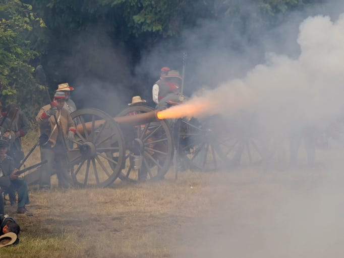 A Confederated Army cannon fires during a battle at the annual Civil War reenactment at Willamette Mission State Park on Saturday, July 5, 2014.