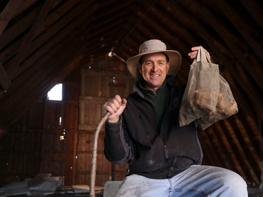 Greg Rinehart of Rinehart's Family Farm, hoists up a bag of freshly picked morel mushrooms on Friday, May 2, 2014, at his farm outside Odgen, Iowa in rural Boone County.