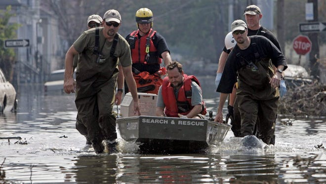 Workers use a boat to rescue a man from his flooded home on Sept. 15, 2005, after Hurricane Katrina hit New Orleans.