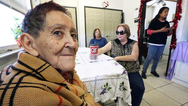 Resident Alicia Guzman, foreground, sits in the living area of a shelter operated by the Opportunity Center for the Homeless. She is with other residents, including Emily Rodriguez, center with glasses and Carmen Rangel, background. At far right is Lety Brewer, a resident support counselor.