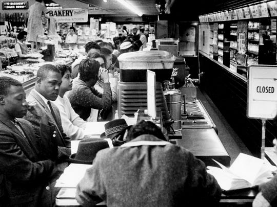 """The """"closed"""" sign goes up as soon as black college students sit at the counter of the downtown Woolworth's on Feb. 27, 1960. Later at the store, a group of white boys attacked two black demonstrators after receiving no response from their insults."""