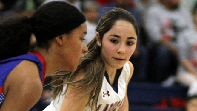 Junior Lady Cat Valerie Lopez shadows Las Cruces guard Janessa Johnson during Tuesday's  varsity basketball game at Deming High School. The Bulldawgs picked up a 54-20 victory.