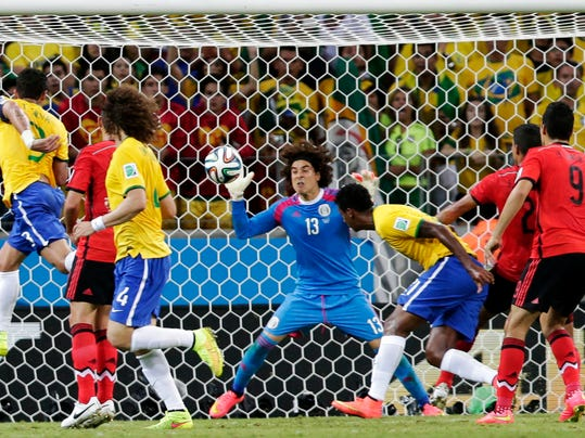 Mexico's goalkeeper Guillermo Ochoa (13) bats the ball away after a header by Brazil's Fred, left, during the group A World Cup soccer match between Brazil and Mexico at the Arena Castelao in Fortaleza, Brazil, Tuesday, June 17, 2014.  (AP Photo/Marcio Jose Sanchez)