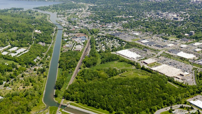 Ithaca's flood control channel runs from southwest Ithaca and northeast toward the State Street Bridge, center left, to Cayuga Lake, top left. The large building at the lower right is Walmart. A sediment management facility to de-water dredging spoils is planned behind Walmart. SIMON WHEELER / Staff Photo
