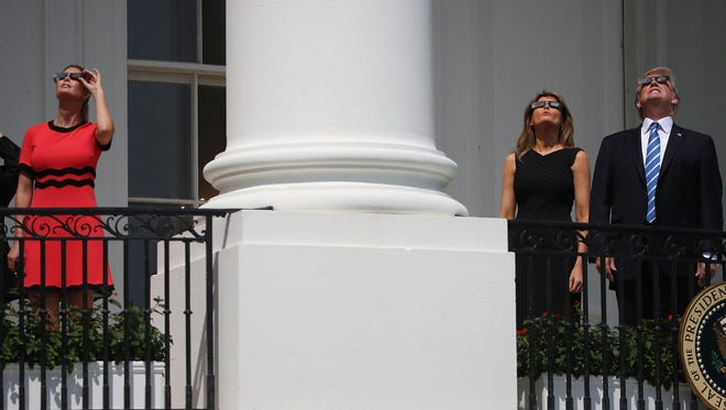 Ivanka Trump chose a tomato red dress with black accents by Gucci for the solar eclipse-watching interlude on Aug. 21, 2017.