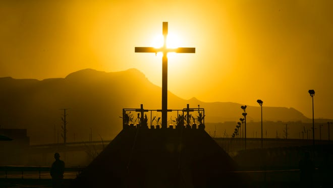 The sun sets on a cross at a praying platform on the banks of the Rio Grande River near the fairgrounds in Juarez, Mexico, on Tuesday evening, Feb. 16, 2016.