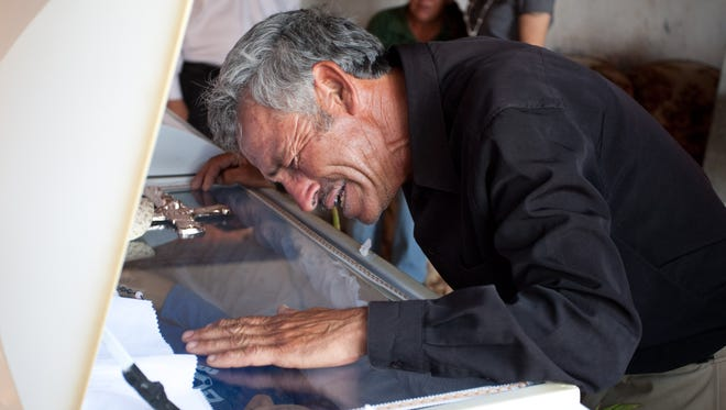 Overcome with grief, Jesús Hernández, father of Sergio Adrián Hernández Güereca, 15, shot to death by a Border Patrol agent in June 2010, weeps over his son's coffin at the family home in Juárez.