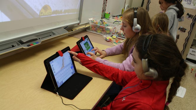 From left: Madelyn Hayes, 9, of Port Crane, and Alaina Hamilton, 10, of Binghamton, complete a web-coding game on iPads.