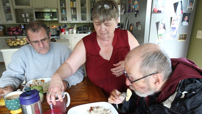 In this Sept. 28, 2017 photo, Judy Willis serves lunch to two of her foster care residents in her northwest Rochester, Minn., home. Willis and her husband have set up their home with space for several foster care adults.
