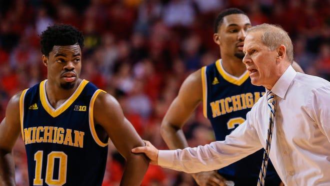 Michigan coach John Beilein talks to Derrick Walton Jr. (10) with Zak Irvin (21), rear, during the second half of an NCAA college basketball game against Nebraska in Lincoln, Neb., Saturday, Jan. 23, 2016. Michigan won 81-68.