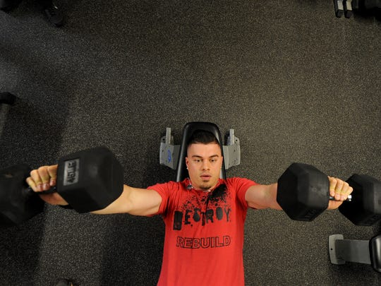 Austin Britton works out with dumbbells on Wednesday