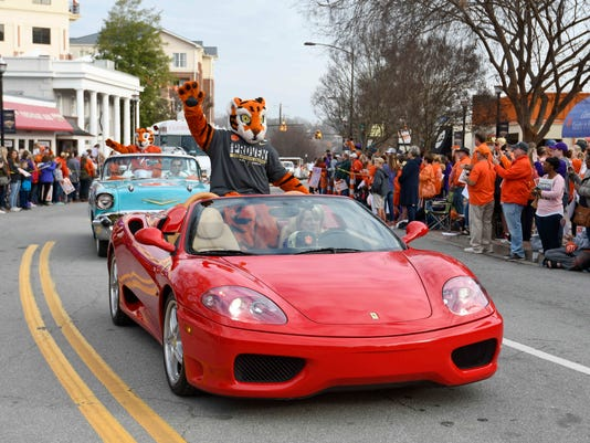 """The Clemson mascots """"Tiger"""" and """"Cub"""" wave to the crowd during a parade honoring the NCAA college football champions, Saturday, Jan. 14, 2017, in Clemson, S.C. Clemson won the title with a 35-31 victory over defending national champ Alabama last Monday night. (AP Photo/Richard Shiro)"""