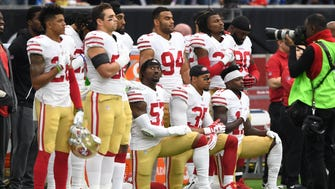 San Francisco 49ers outside linebacker Eli Harold (57), strong safety Eric Reid (35), and wide receiver Marquise Goodwin (11) kneel for the national anthem prior to the game against the Houston Texans at NRG Stadium.