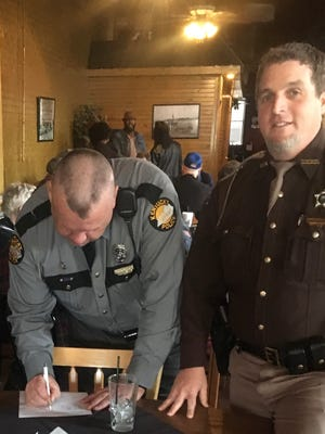 Russell Roberts of Kentucky State Police and Michael Heady of Union County Police sign the document.