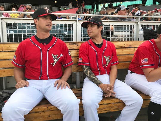 El Paso Chihuahuas pitcher Robert Stock, left, sits