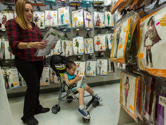 Crystal Moreno, 29, and Diesel Rojas, 2, look over the costumes at ABC Party World, 1021 E. Amador Ave. on Tuesday, October 4, 2016. In Las Cruces, party stores and stores specializing in Halloween costumes, accessories and decorations anticipate good sales.