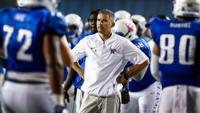 Dejected University of Memphis head coach Mike Norvell (middle) looks on as the offense leaves the field after losing a fumble to the University of Tulsa defense during third quarter action at the Liberty Bowl Memorial Stadium.