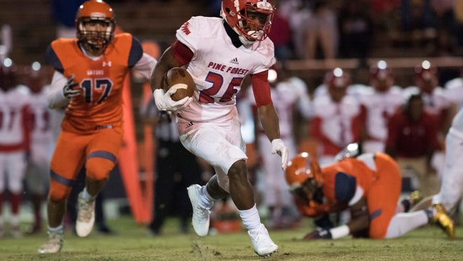 Pine Forst HIgh School running back  Anwar Lewis, (No. 25) slips past the Escambia High School defense for a modest gain during Friday night's District 1-6A football playoffs.