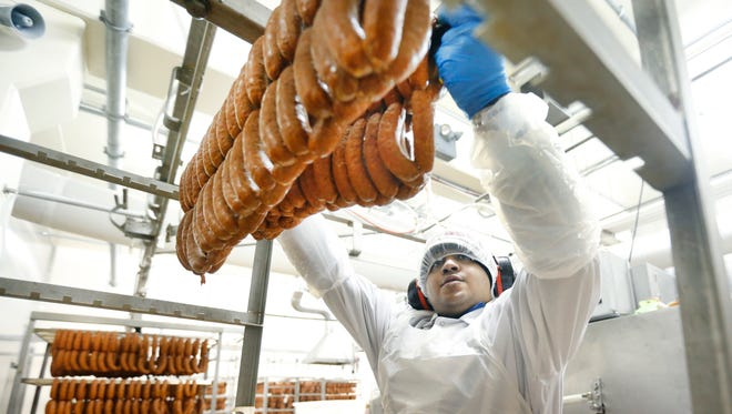 Luiz Martinez moves pork-andouille sausages at Zweigle's in Rochester, where the company is expanding its assembly line and new products.