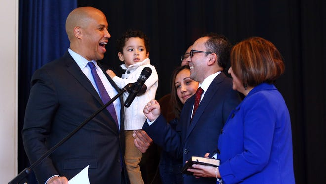 U.S. Senator Cory Booker smiles while holding 3-year-old Josiah Morales after swearing in Josiah's grandfather, Morristown's first Latino councilman David Silva as wife Patricia holds the Bible during  Morristown's 2018 reorganization meeting at the Thomas Jefferson School. January 1, 2018. Morristown, NJ.