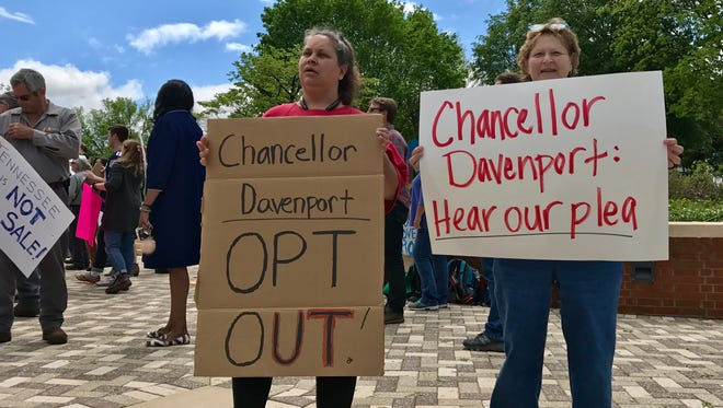 Tammy Shultz, left, and Vera Spencer hold signs calling on University of Tennessee Chancellor Beverly Davenport to reject outsourcing on the Knoxville campus on April 24, 2017.