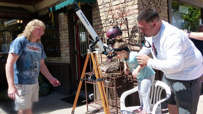 A father helps position his daughter to be able to see the progress of the eclipse on a telescope at Earth N Stone stationed by owner Alan Miner. The family was visiting from Lubbock, Texas.