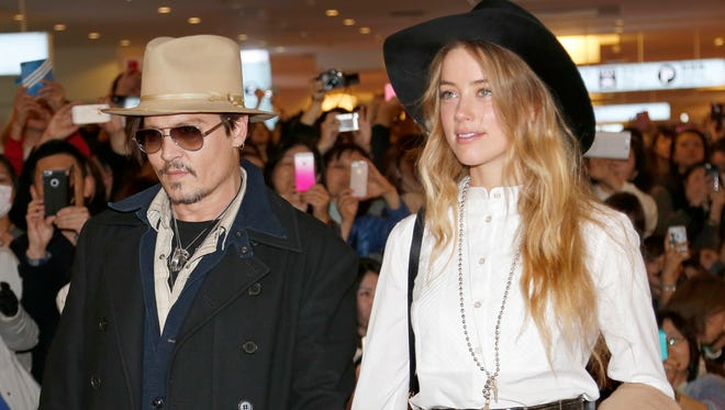 """Johnny Depp and Amber Heard arrive at Haneda international airport in Tokyo to promote his film """"Mortdecai"""" in January 2015."""