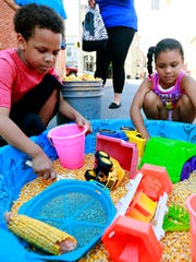Camiran Hay, 8, left, and Aubriana Anderson, 4, both of York City, play in the corn box during National Night Out in York City, Tuesday, Aug. 1, 2017. Dawn J. Sagert photo